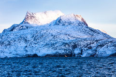 Huge Sermitsiaq mountain covered in snow with blue sea and small. Fidhing boat in the foreground, nearby Nuuk city, Greenland Royalty Free Stock Photography