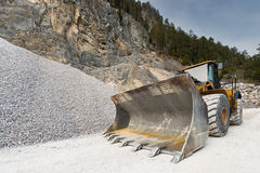 Huge shovel of wheel loader. At stone quarry with gravel hill Stock Photo