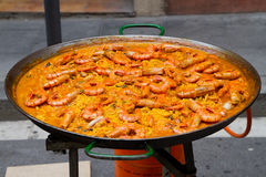 Huge shrimp paella in cooking pan. Huge paella with shrimp in a cooking pan at a street festival stock image