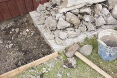 A huge sledgehammer breaks cement into stones royalty free stock photography