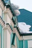 A huge snow block hangs from the roof above the entrance to the building. royalty free stock image