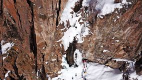 A huge snow cliff. Flows down the waterfall. Huge icicles and ice. royalty free stock photography