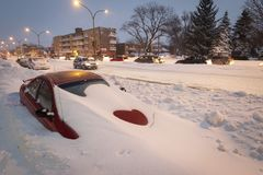 Buried car in street during snow storm in Montreal Canada stock image