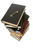 Huge stack of books with key. Huge stack of books with a skeleton key on top to signify the key to knowledge can be found in books Stock Photo