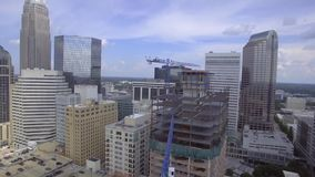 Huge steel modern urban skyscrapers under crane construction site in middle center of big city in 4k aerial shot stock video