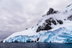 Huge steep stone rock covered with blue glacier and cloud with w Royalty Free Stock Image