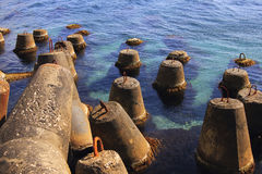 Huge stone anchor in the blue sea. Huge stone anchors near the beach in the blue sea Stock Images