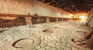 Huge stone cellar with aged wine bottles and qvevri, large earthenware vessels under ground. Rural storage of winery. Huge stone cellar with aged dust wine stock photography