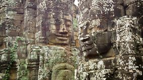 Huge stone faces on the towers of the ancient temple. Bayon, Angkor, Cambodia stock footage