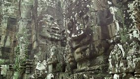 Huge stone faces on the walls of an ancient temple. Cambodia, Bayon stock video