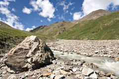 Huge stone near mountain river. Caucasus valley. Stock Image