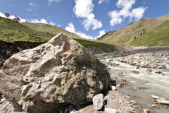 Huge stone near mountain river. Caucasus valley. Royalty Free Stock Image