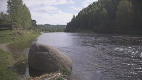 Huge stone perched near riverbank, dark forest is across the river. Roundish big rock rises at left bank. It is fenced off a part of river and formed small bay stock footage