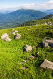 Huge stones in valley on top of mountain range. Mountain summer landscape. meadow with huge stones among the grass on top of the hillside near the peak of Stock Photography