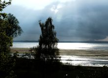 Huge storm cloud with sunbeams over the lake