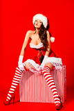 Huge surprise. Beautiful young woman in Santa Claus costume posing with a huge gift box over red background. Christmas Royalty Free Stock Images