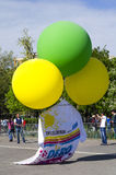 Huge T-shirt lifted by colored balloons Stock Photos