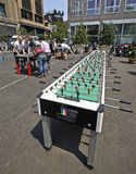 Huge table foosball. MILAN, ITALY- JUNE 11, 2015: A huge table foosball allows twenty players have fun. In the background are classic kickers. Initiative of the stock image
