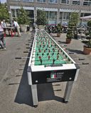Huge table foosball. MILAN, ITALY- JUNE 11, 2015: A huge table foosball allows twenty players have fun. In the background are classic kickers. Initiative of the stock photography