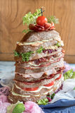 Huge tasty sandwich. Big sandwich with meat and vegetables served on the table,selective focus Royalty Free Stock Image