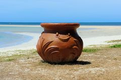 Huge terracotta pot on the seashore. Royalty Free Stock Photo