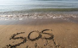 Big text SOS on the sand of the beach. Huge text SOS on the sand of the beach Royalty Free Stock Image