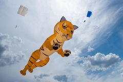 Huge tiger kite flyes in the cloudy sky. Royalty Free Stock Photo