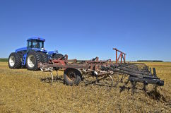 Huge tractor pulling a field cultivator. The stubble of a wheat field is being turned over by a large blue tractor pulling a field cultivator Stock Images