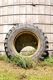 Huge tractor tire leans on silo. Av very old silo serves as support to a large tractor tire and rim Stock Image