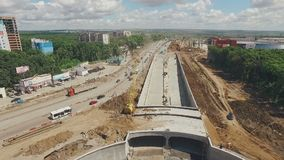 Huge traffic roundabout under construction and long road, aerial shot, drone is flying along. Many of dust, summer day, in Russia stock video