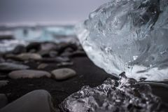 Big piece of ice on a black beach. Huge transparent piece of ice on black rocks volcanic beach in Iceland, black and white Royalty Free Stock Photo