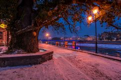 Huge tree and lantern on the winter embankment. Beautiful evening on the river with some ice and snow on the shore Stock Photo