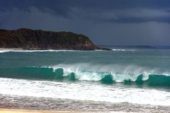 Tropical storm over the beach with surf. Huge tropical thunderstorm over Blackhead Beach, New South Wales, Australia, with breaking wave foreground Royalty Free Stock Photography