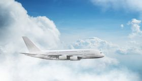 Huge two-storey passengers commercial airplane flying above dramatic clouds. Travel and business concept stock photography