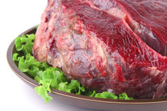 Huge uncooked meat on plate Stock Images