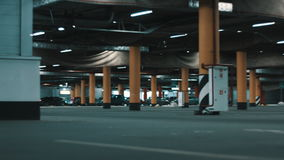Huge underground parking. Motion shot of huge underground mall parking with cars and illumination stock footage
