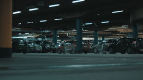 Huge underground parking. Motion shot of huge underground mall parking with cars and illumination stock video footage
