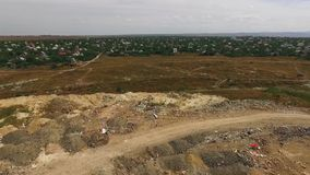 Huge Urban Waste Dump At Suburb In Ukraine. This is an aerial rotating shot over huge city waste dump surrounded by the city buildings in greenery.  There is one stock video footage