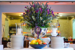 A huge vase of flowers on decorated table in the restaurant. Stock Photos