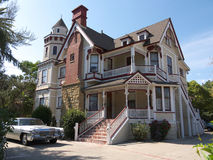 Huge Victorian house. Brown and cream color with stairs leading to porch. Old car parked in front Royalty Free Stock Photos