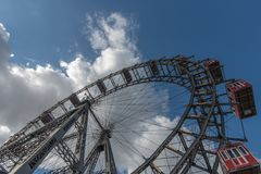 A huge Victorian Metal Ferris Wheel in a large public park in Vi. Enna, Austria with a blue sky and white fluffy clouds above Royalty Free Stock Images