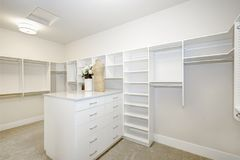 Huge walk-in closet with shelves, drawers and clothes rails. Huge white walk-in closet with shelves, drawers and clothes rails. Northwest, USA royalty free stock photography