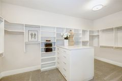 Huge walk-in closet with shelves, drawers and clothes rails stock image