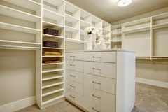 Huge walk-in closet with shelves, drawers and shoe racks. royalty free stock photography