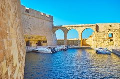 The wall of Fort St Angelo, Birgu, Malta. The huge wall and scenic arched bridge of Fort St Angelo, neighboring with a tiny haven, occupied with motor boats Stock Photo