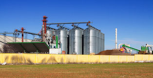 Huge warehouse facilities for agricultural sector. Under clear blue sky near field Stock Photos