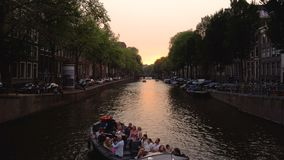 Huge water boat traffic on water chanel in Amsterdam city at sunset time. Popular Travel Destination. Cloudy weather stock video