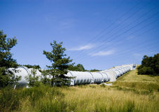 Huge water pipe. A huge water pipe of a water power plant, cutting across a grass hill with some trees Royalty Free Stock Photo