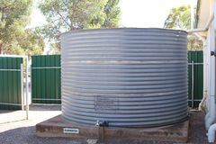 Huge water reservoir with rain water in the Australian Outback. Huge water reservoir with rainwater to deliver drinking water in the hot and dry climate of the Stock Photo