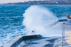Huge wave crushing on pier Stock Photo